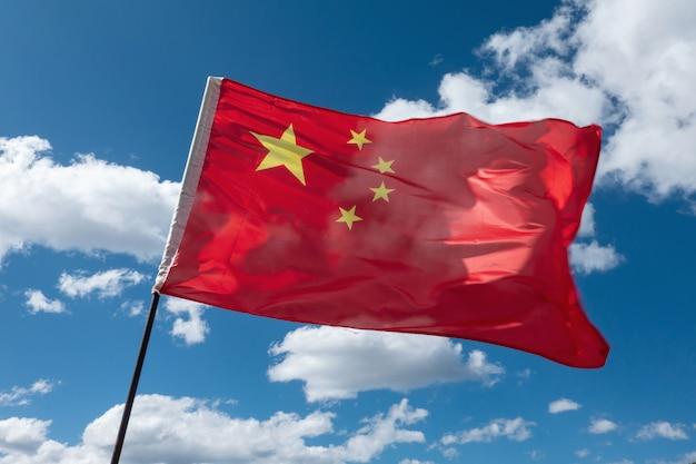 De chinese vlag zwaaide in de wind in de blauwe lucht.