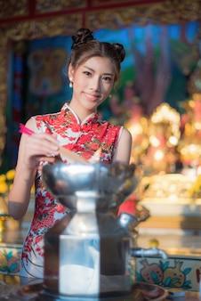 De chinese vrouw kleedt traditionele cheongsam bij chinese tempel.