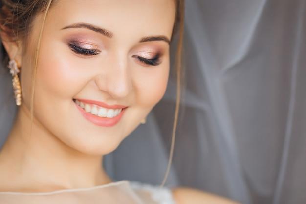 De chique bruid in zachte make-up kijkt naar beneden en glimlacht