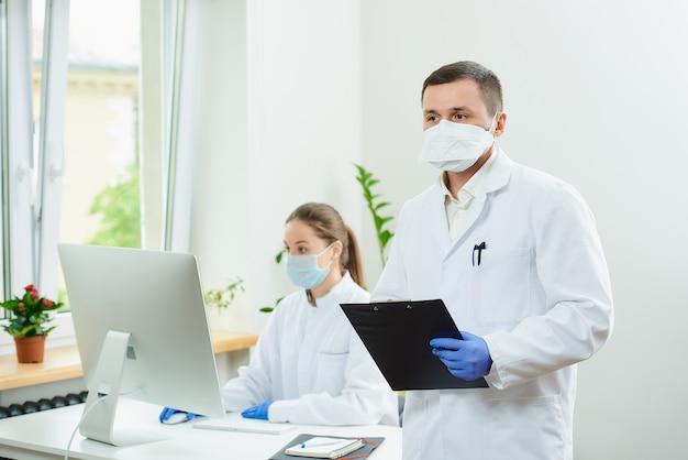 De chirurg draagt een gasmasker en medische wegwerphandschoenen met een klembord