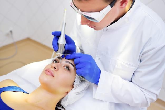 De chirurg schoonheidsspecialiste verwijdert pigmentatie en vaatnetten op de huid van de patiënt - een mooie jonge vrouw neodymium laser