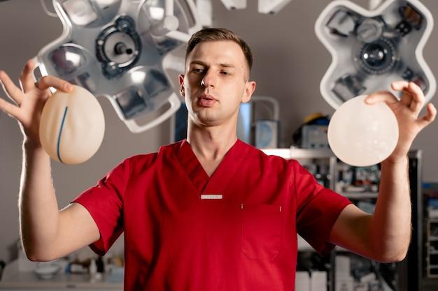 De chirurg toont verschillende soorten siliconenimplantaten. borstvergroting operatie.