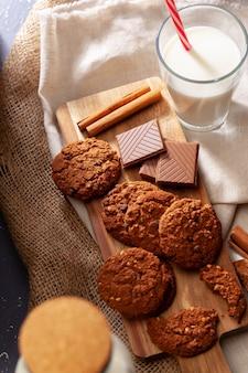 De chocolade knapperige koekjes met glas melk sluiten omhoog