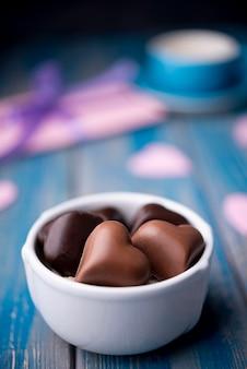 De chocolade van de valentijnskaartendag in kop met defocused heden