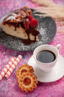 De chocoladetaart van de vooraanzichtaardbei met kop thee en koekjes op het roze zoete koekje van de bureausuiker