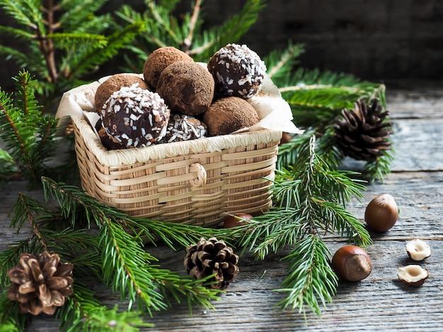 De chocoladetruffels van kerstmis in een rieten vakje de spar vertakt zich op houten lijst