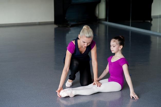 De choreograaf leert het kind de juiste houding.