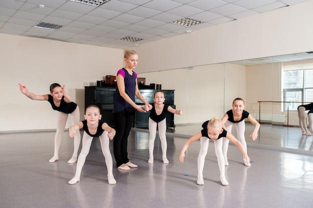 De choreograaf leert kinderen dansen.