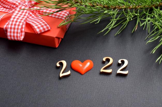 De cijfers van het nieuwe jaar 2022 en een rood geschenk met een kersttak.