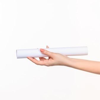 De cilinder in vrouwelijke handen op witte muur