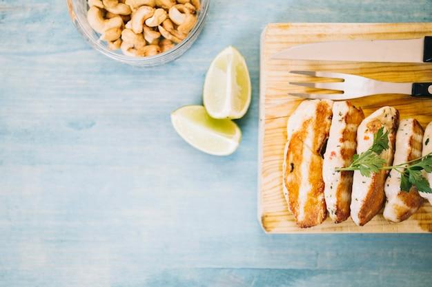 De citroen snijdt dichtbij vlees op houten raad