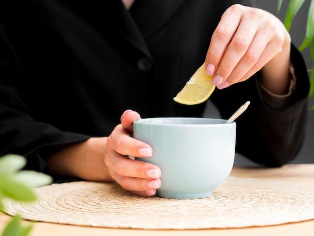 De citroenplak van de vrouwenholding over theekopje