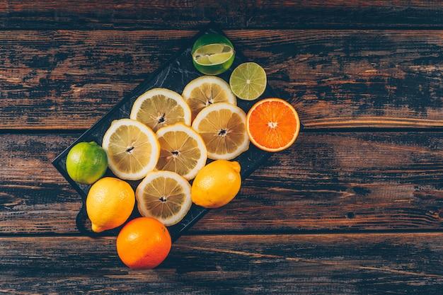 De citroenplakken met sinaasappelen en groene citroenvlakte leggen op een scherpe raad en een donkere houten ruimte als achtergrond voor tekst