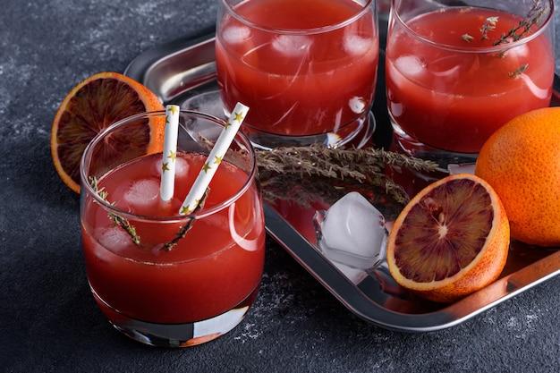 De citrusvruchtensap van de close-upzomer van rode sinaasappelen met ijs in glazen op dienblad op grijze achtergrond