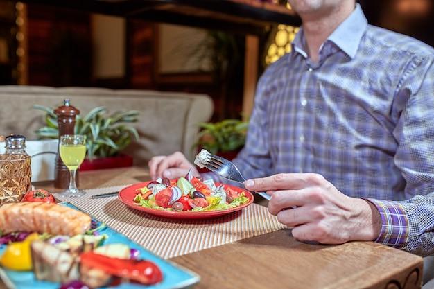 De cliënt die smakelijke griekse salade in restaurant eten, sluit omhoog.