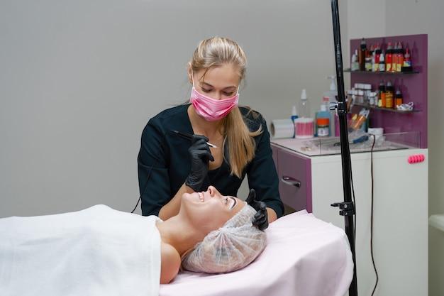 De cliënt van het kosmetiekabinet ligt op de bank. schoonheidsspecialiste brengt permanente inkt aan op wenkbrauwen. procedure voor permanente wenkbrauwmake-up. vrije ruimte. schoonheidsindustrie