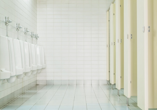 De close-up betegelt muur in het toilet van de mens met toiletmening door urinoirs en kleine ruimte
