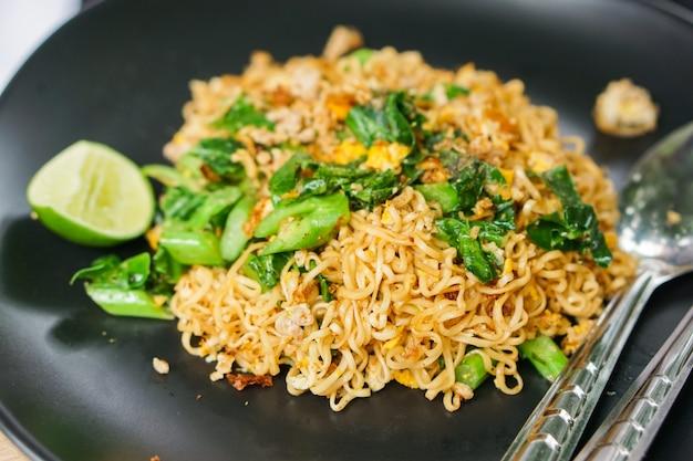 De close-up beweegt gebraden mama of thaise phat gebraden noedels met gesneden citroen en groenten