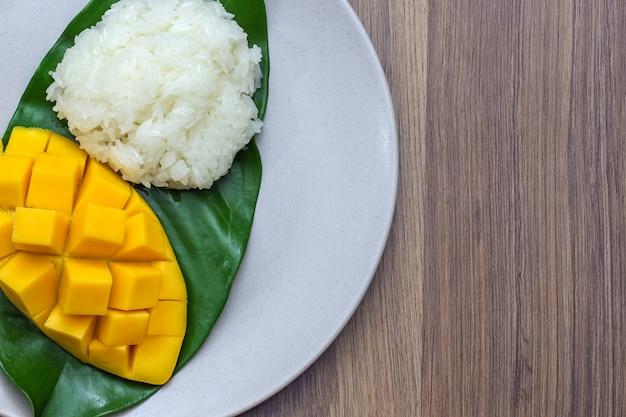 De close-up macroschotschotel van snijdt mooie gele mango met kleverige rijst op houten lijst