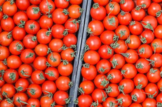 De close-up overvloed rode verse rijpe kersentomaten samen met stammen wachten op distributie in doos op landbouwersmarkt.