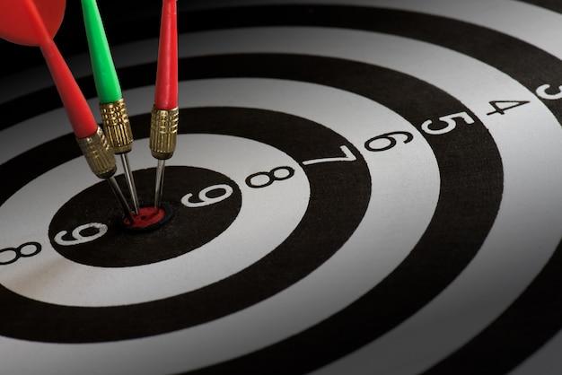 De close-up schoot rode en groene pijltjepijlen op centrum van dartboard, het concept van het doelsucces.