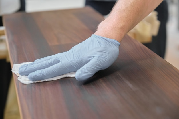 De close-up van arbeider dient beschermende handschoenen met het eindigen van dekking in