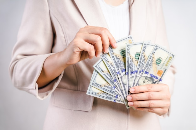 De close-up van bedrijfsvrouw overhandigt tellend geld ons dollarrekeningen op wit. geld concept.