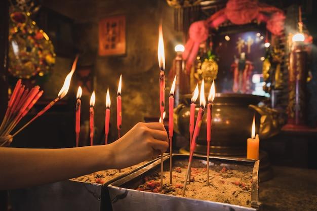 De close-up van de hand houdt de rode kaarsen in de oude wierookpot.