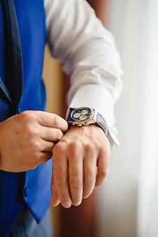 De close-up van de mens in vrijetijdskleding kijkt zijn horloge