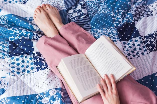 De close-up van de vrouw draagt pyjama en ontspant thuis en leest een boek