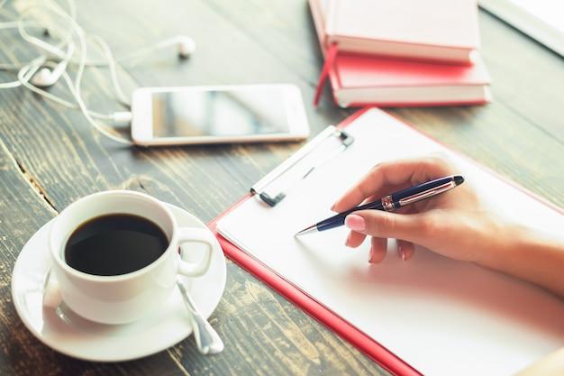 De close-up van een bedrijfsvrouwenhand schrijft op een lege ontwerper bij koffie.