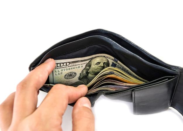 De close-up van een hand trekt dollars uit een portefeuille