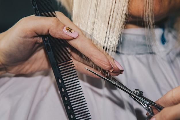 De close-up van een kapper snijdt nat wit haar van een cliënt in een salon. kapper snijdt een vrouw. zijaanzicht van een hand die haar met schaar snijdt.