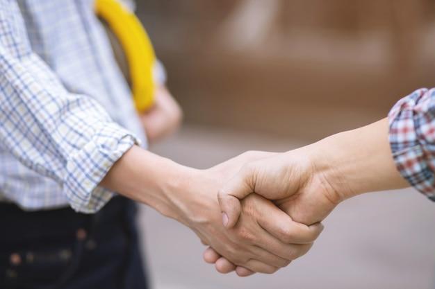 De close-up van een schud van de bedrijfsmensenhand tussen twee collega's begroet, vertegenwoordigt vriendschap is goed, succes, gefeliciteerd. buiten van gebouw. kopie laat ruimte voor tekst.