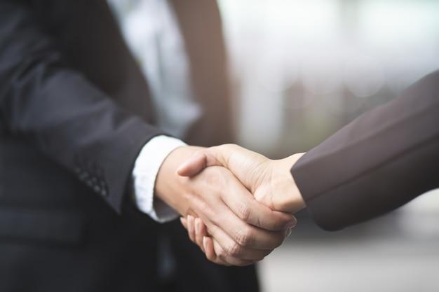 De close-up van een zakenmanhand schudt onderneemster tussen twee ok collega's