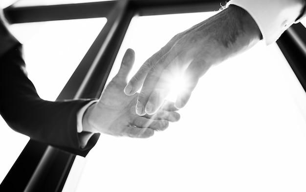 De close-up van handen die vennootschapvergadering schudden