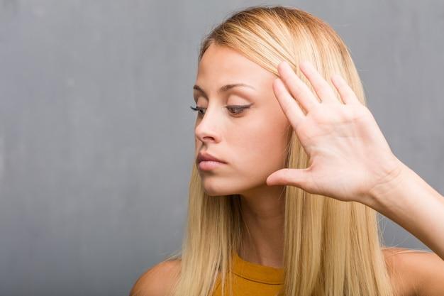 De close-up van het gezicht, portret van een natuurlijke jonge ernstige en bepaalde blonde vrouw, die hand vooraan zet, houdt gebaar tegen, ontkent concept