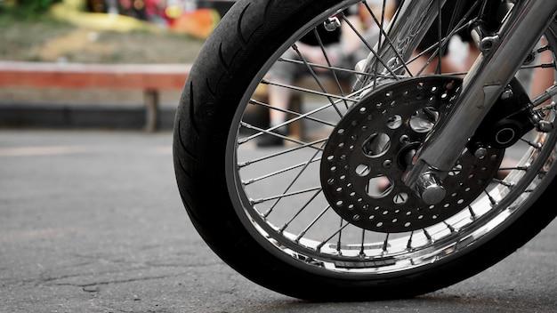 De close-up van het motorfietswiel op een wazig achtergrondwiel op asfalt