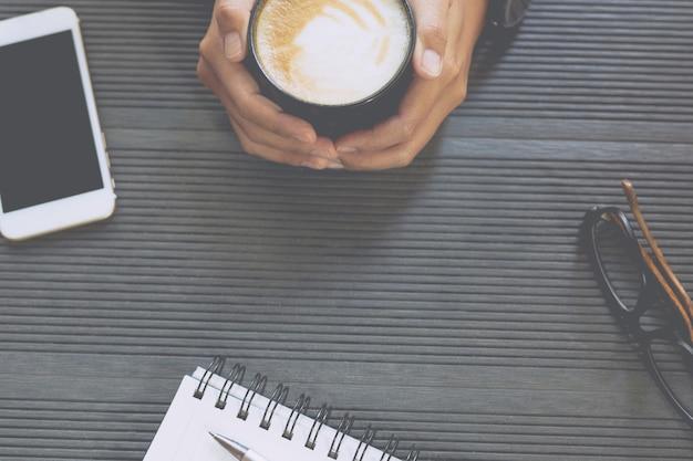 De close-up van mensen bedrijfsvrouw zit drinkt koffiekop. bureautafel met boek kladblok, telefoon, leverancier van apparatuur in het werk bovenaanzicht met kopie ruimte. concept om te werken in een moderne kantoorlevensstijl