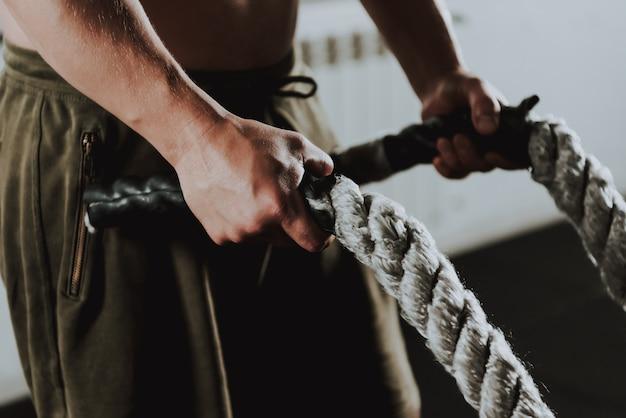 De close-up van sportman oefent in gym alleen uit