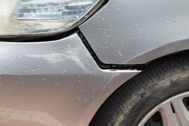 De close-up van verpletterde auto raakte op de voorbumper weg, gebeurt het ongeval op regenende dag
