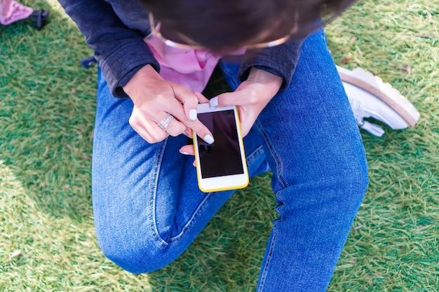 De close-up van vrouwelijke handen houdt cellphone in openlucht op de straat. vrouw met behulp van mobiele smartphone.