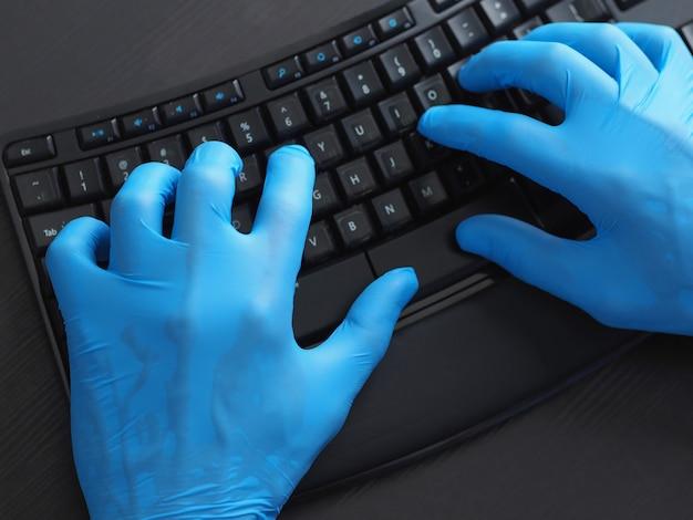 De close-up van zwart computertoetsenbord en dient blauwe latexhandschoenen in.