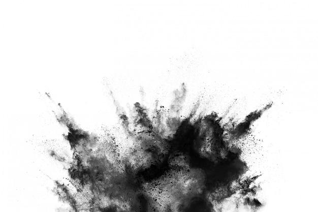 De close-up van zwarte stofdeeltjes explodeert geïsoleerd op witte achtergrond.