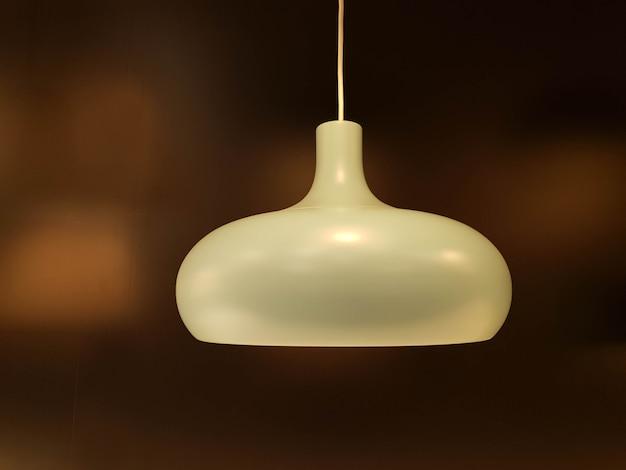 De close-up verfraait de witte lamp van het huisplafond op onscherpe bruine achtergrond.