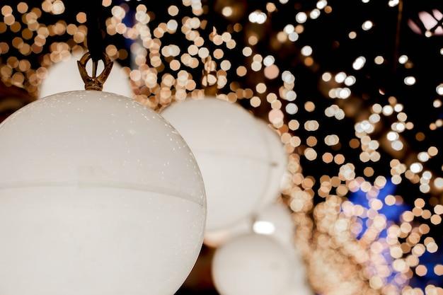 De close-up verfraait kerstmislampen hangt binnenlandse tunnellichten op vaag en bokeh van geleide bezinningsbliksem op nachtachtergrond.