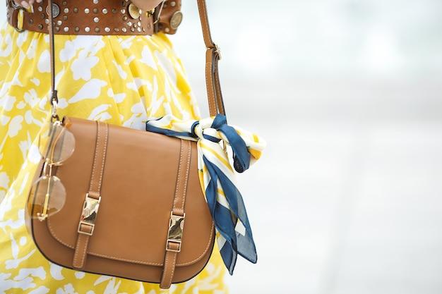 De close-upbeeld van vrouwentoebehoren. portemonnee, zonnebril en de hoofddoek. bruine handtas met modieuze details.