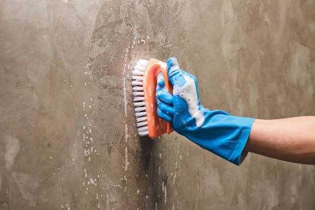 De close-uphand die blauwe rubberhandschoenen draagt wordt gebruikt om schrobben op de concrete muur om te zetten.