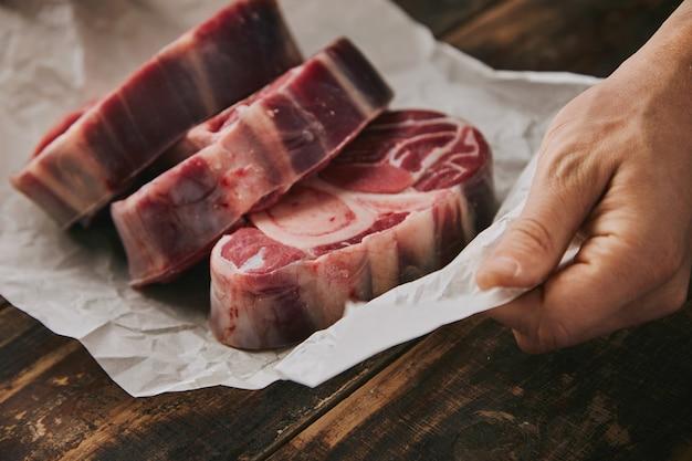 De close-uphand houdt wit kraftpapier vast met drie ruwe grote beenlapjes vlees met been erop, alles op oude houten geborstelde lijst
