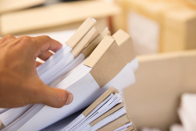 De close-uphand kiest gestapeld document op opslagruimte.